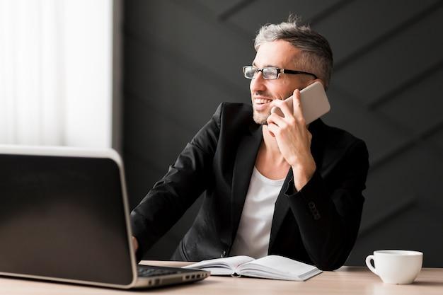 Homem com jaqueta preta, olhando para longe e segurando o telefone móvel