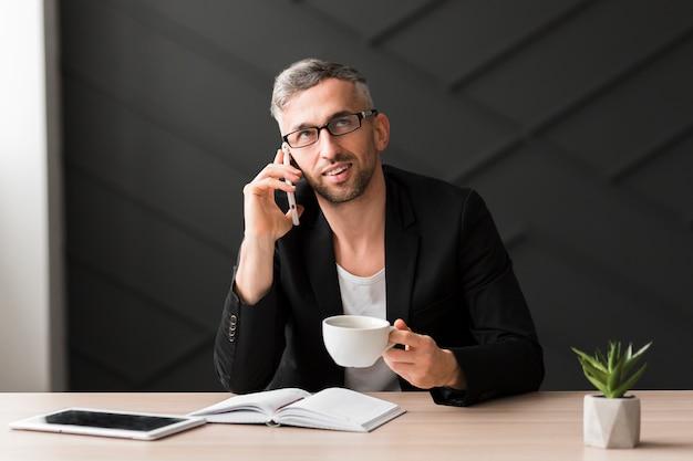 Homem com jaqueta preta, olhando para longe e segurando uma xícara