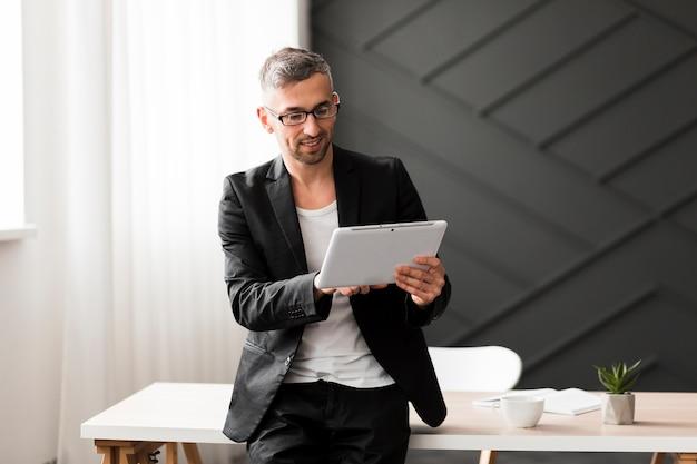 Homem com jaqueta preta, olhando para tablet
