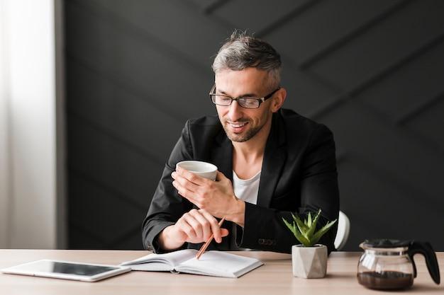 Homem com jaqueta preta, olhando para uma xícara branca