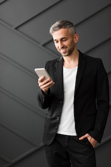 Homem com jaqueta preta, sorrindo para o seu telefone móvel