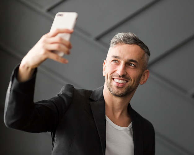 Homem com jaqueta preta tomando uma selfie