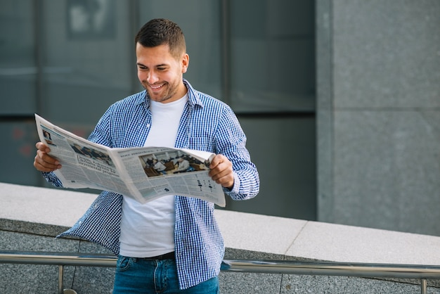 Homem com jornal apoiado no corrimão