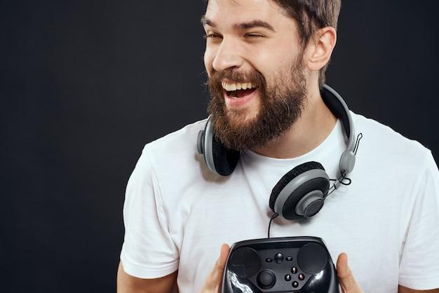 Homem com joystick nas mãos em um fundo escuro e isolado