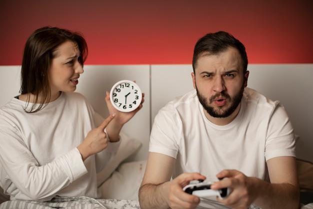 Homem com joysticks jogando videogame na cama à noite, ignorando sua esposa