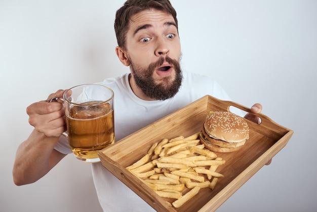 Homem com junk food junk food, hambúrguer e batatas fritas