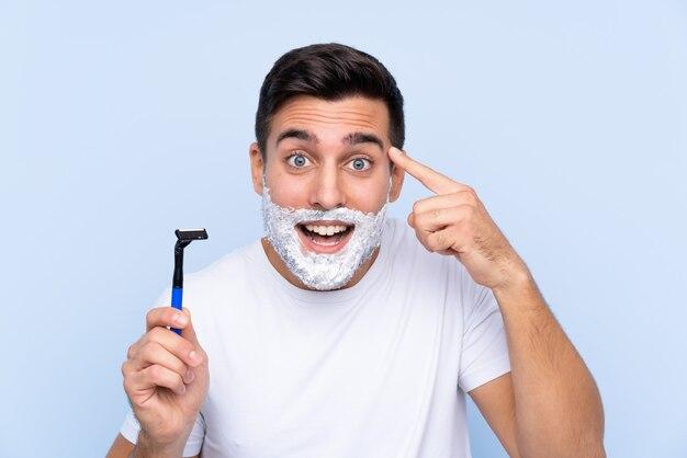 Homem com lâmina de barbear sobre parede azul isolada