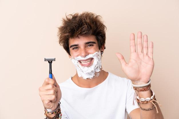 Homem com lâmina de barbear sobre parede isolada