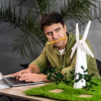 Homem com lápis na boca trabalhando em um projeto de energia eólica ecologicamente correto