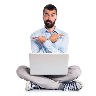 Homem com laptop apontando para as laterais com dúvidas