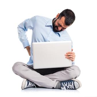 Homem com laptop com dor nas costas