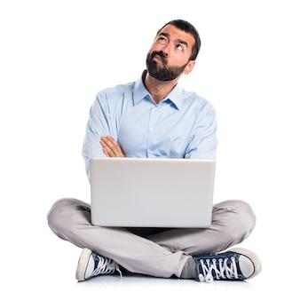 Homem com laptop com dúvidas