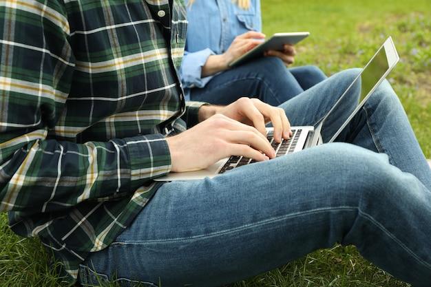 Homem com laptop e mulher com tablet trabalham no parque. trabalho ao ar livre