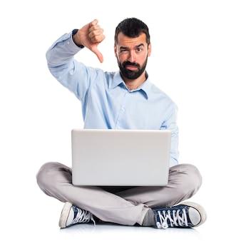 Homem com laptop fazendo sinal ruim