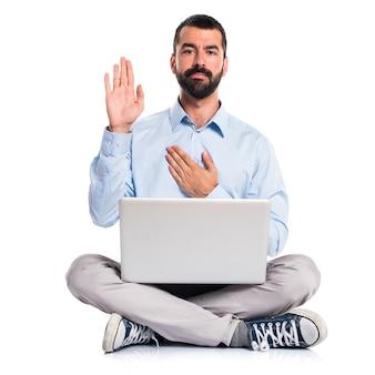 Homem com laptop fazendo um juramento