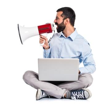 Homem com laptop gritando por megafone