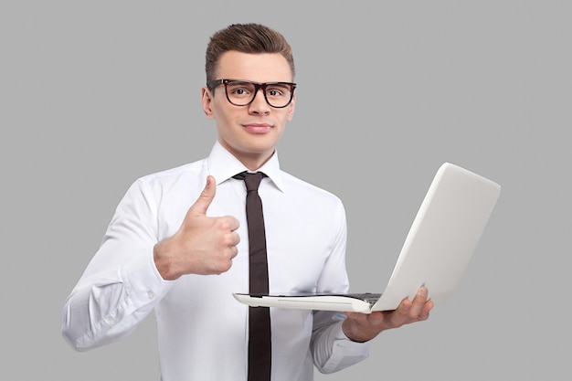 Homem com laptop. jovem bonito de camisa e gravata segurando um laptop e gesticulando em pé contra um fundo cinza
