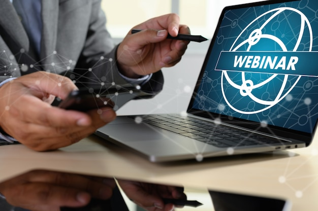 Homem com laptop mostrando webinar na tela