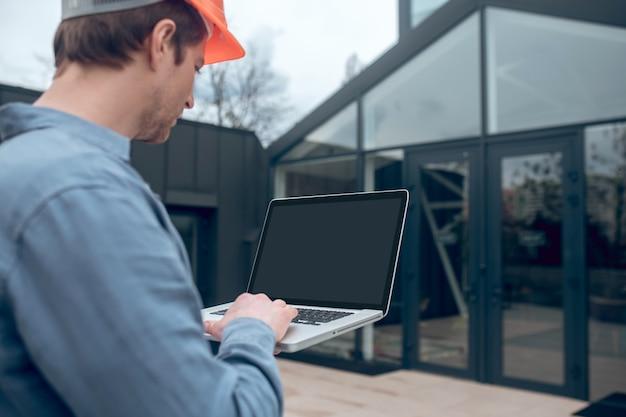 Homem com laptop na frente de uma casa inteligente