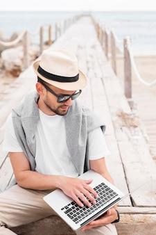 Homem com laptop no cais da praia