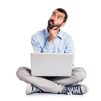 Homem com laptop pensando
