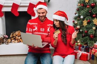 Homem, com, laptop, perto, mulher, com, cartão plástico