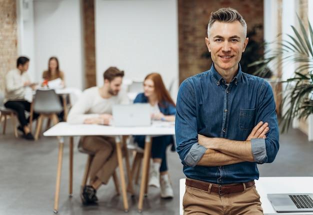 Homem com laptop posando ao lado de colegas de trabalho