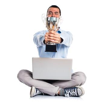 Homem com laptop segurando um troféu