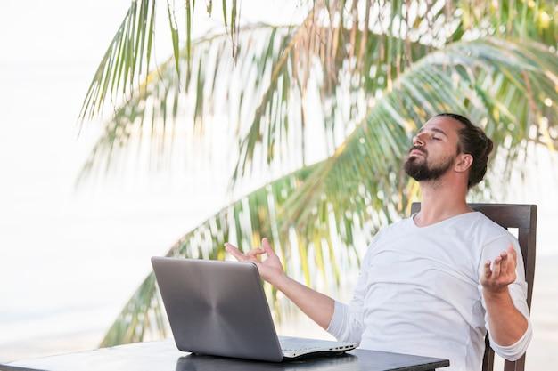 Homem com laptop, sentado em um café na praia perto de palmeiras e fazendo ioga