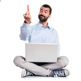 Homem com laptop tocando na tela transparente