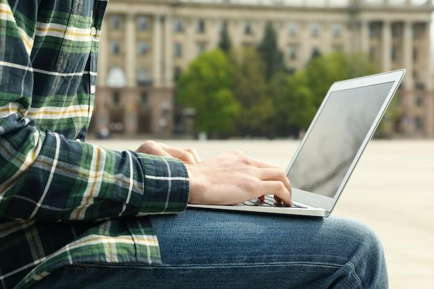 Homem com laptop trabalha ao ar livre. horário de trabalho grátis