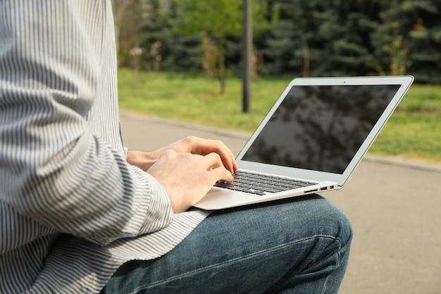 Homem com laptop trabalha no parque. trabalho ao ar livre