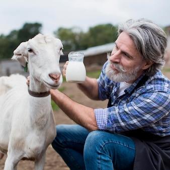 Homem com leite de cabra fresco