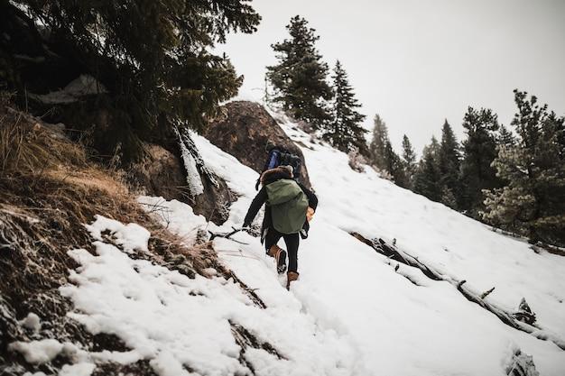 Homem, com, lenha, escalando, nevado, colina