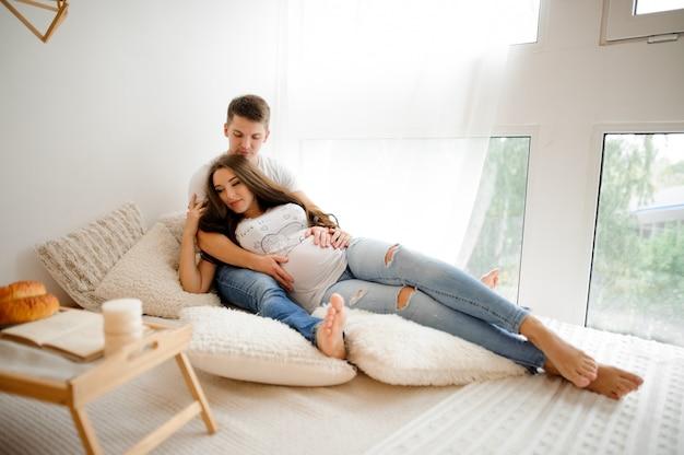 Homem com linda mulher grávida deitada na cama em um quarto branco