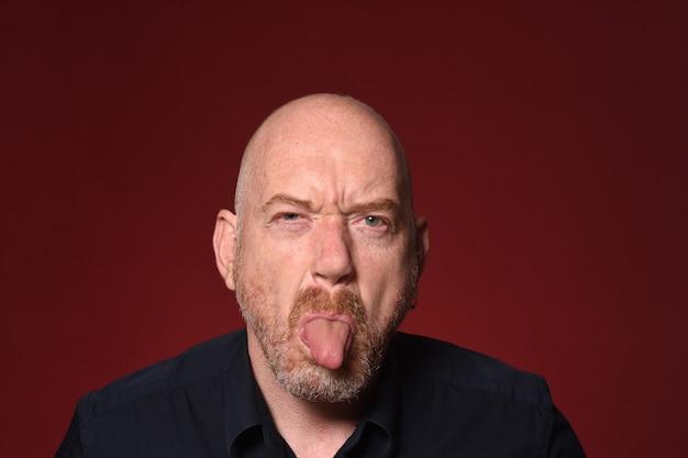 Homem com língua em fundo vermelho