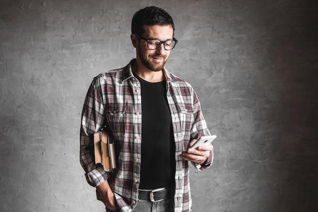 Homem com livros e olhando para a tela de um smartphone. conceito de educação