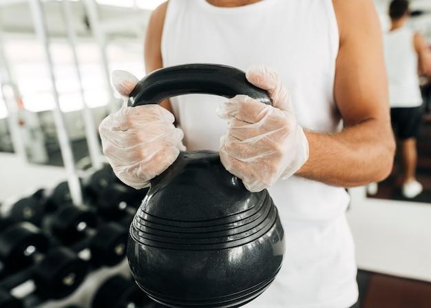 Homem com luvas na academia segurando o equipamento