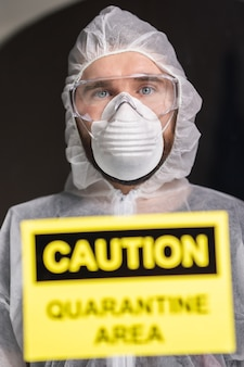 Homem com macacão branco de proteção, máscara e óculos no rosto
