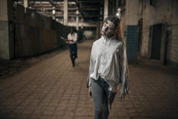 Homem com machado alcançando o zumbi feminino em uma fábrica abandonada, lugar assustador. terror na cidade, rastejadores assustadores, apocalipse do fim do mundo, monstros malignos sangrentos