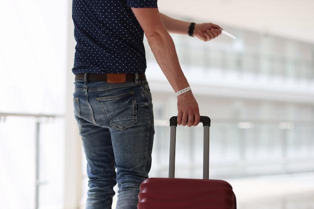 Homem com mala segurando uma chave de plástico para close up de quarto de hotel