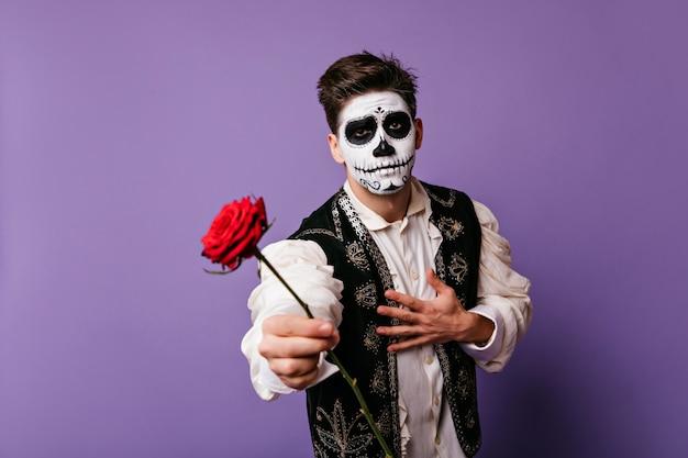 Homem com maquiagem de morto mexicano segurando flor vermelha. cara emocional em roupas tradicionais espanholas.