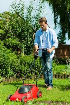 Homem com máquina de cortar relva no seu quintal