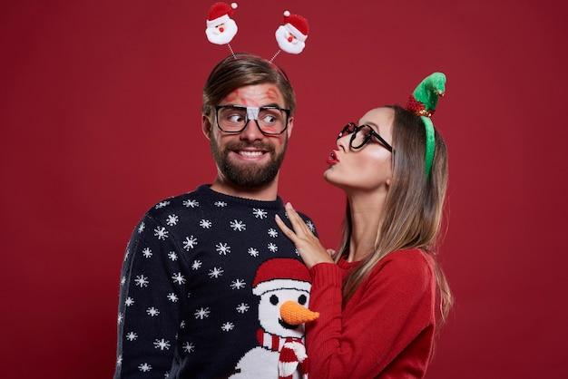 Homem com marcas de beijo no rosto perto da namorada