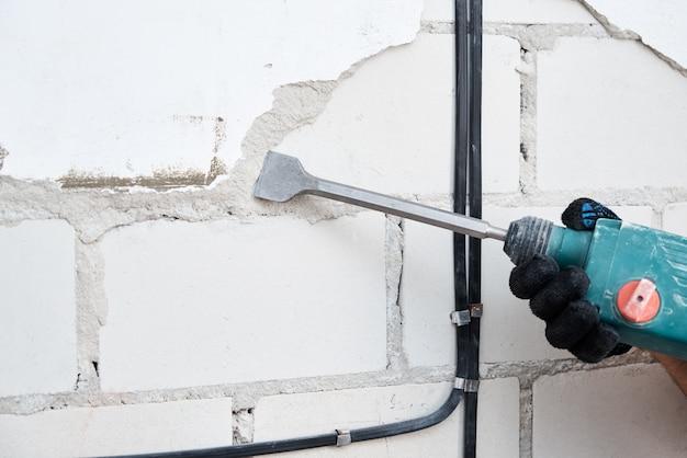 Homem com martelo de demolição remove estuque da parede