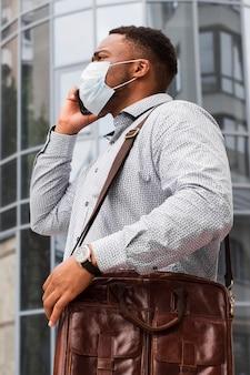 Homem com máscara a caminho do trabalho durante a pandemia e falando ao telefone