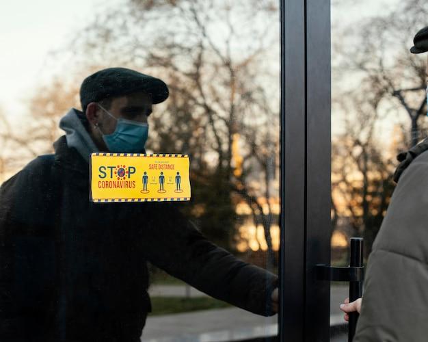 Homem com máscara abrindo porta