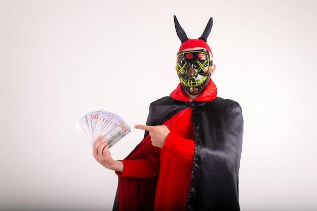 Homem com máscara, chapéu vermelho com chifres de diabo e fantasia de halloween posando com muito dinheiro