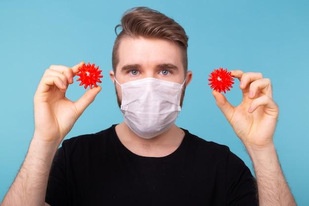 Homem com máscara contra gripe e luvas de proteção segurando um modelo de coronavírus