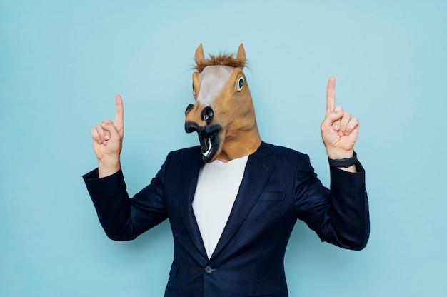 Homem com máscara de cavalo aponta para cima